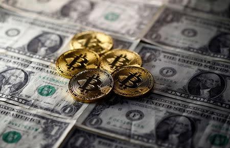 Le monete di Bitcoin (valuta virtuale) disposte sulle banconote del dollaro sono viste in questa immagine dell'illustrazione