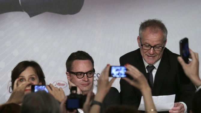 Cannes festival director Thierry Fremaux, right, reads a letter from actor Ryan Gosling explaining why he could not attend the festival, as director Nicolas Winding Refn, centre, and actress Kristen Scott Thomas listen during a press conference for the film Only God Forgives at the 66th international film festival, in Cannes, southern France, Wednesday, May 22, 2013. (AP Photo/Virginia Mayo)