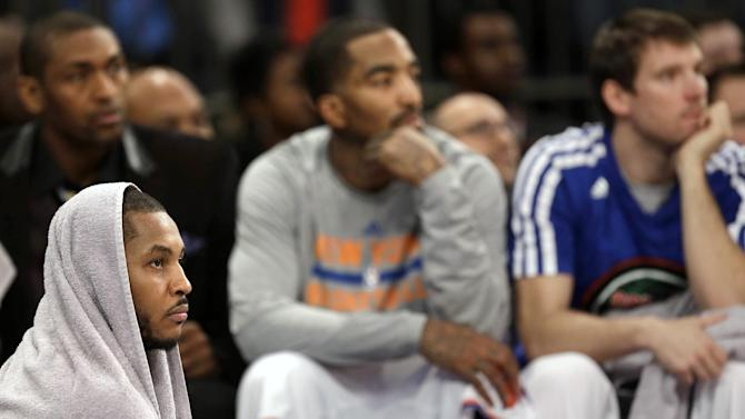 New York Knicks' Carmelo Anthony, left, watches the final minutes of an NBA basketball game against the Brooklyn Nets game from the sidelines at Madison Square Garden, Monday, Jan. 20, 2014, in New York. The Nets defeated the Knicks 103-80