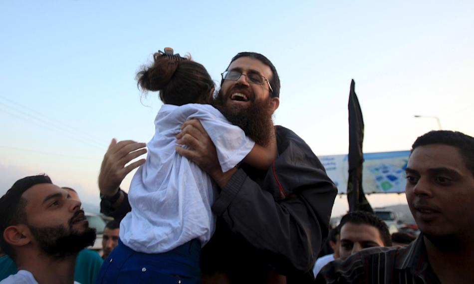 Islamic Jihad leader, Khader Adnan is hugged by his daughter upon his release from an Israeli jail, in the West Bank village of Arabeh near Jenin