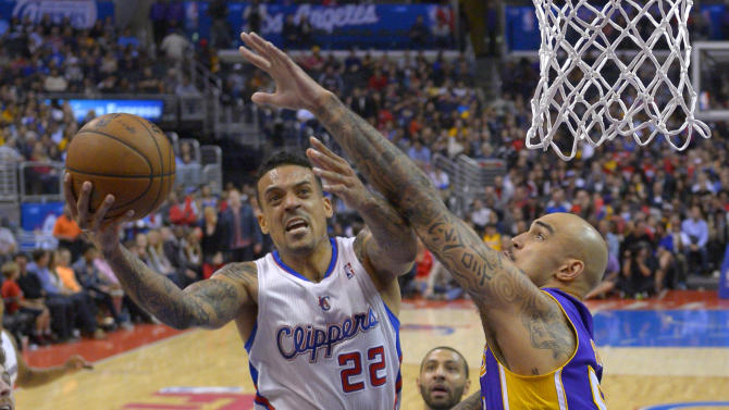 Los Angeles Clippers forward Matt Barnes, left, puts up a shot as Los Angeles Lakers center Robert Sacre defends during the second half of an NBA basketball game, Friday, Jan. 10, 2014, in Los Angeles
