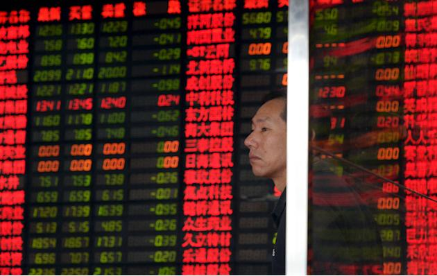 An investor stands in front of an electronic board showing stock information at a brokerage house in Shanghai,