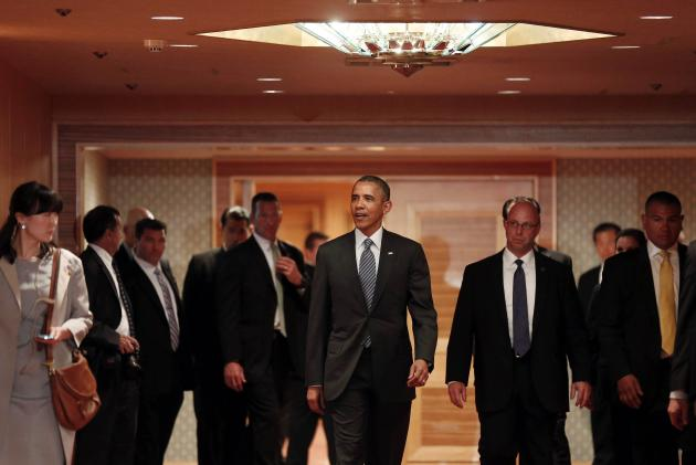 U.S. President Barack Obama walks down a hallway before he bids farewell to Japan's Emperor Akihito at the Okura Hotel in Tokyo