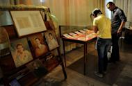 """Students view the restored hand-written novels, the original editions of national hero Jose Rizal's books """"Noli Me Tangere"""" (Touch Me Not) and """"El Filibusterismo"""" (Reign of Greed) at the National Library in Manila in June 2011. Tropical conditions and the library's threadbare budget were big obstacles to saving them for future generations"""