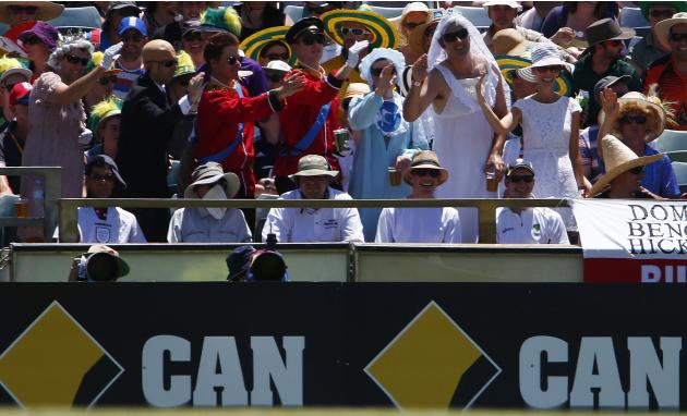 England's fans dress like the Royal Family as they indicate four runs during the second day of the third Ashes test cricket match between England and Australia in Perth