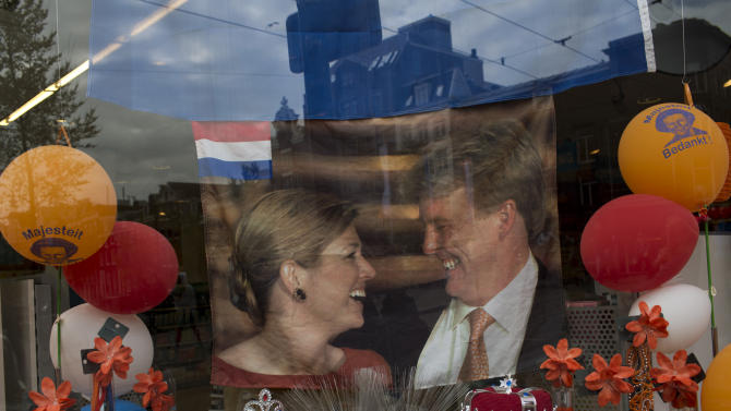 A flag bearing the image of Dutch Crown Prince Willem-Alexander and his wife Princess Maxima is placed on display in a show window along with other Royal memoribilia in downtown Amsterdam, Netherlands Monday, April 29, 2013. Dutch Queen Beatrix has announced she will relinquish the crown on April 30, 2013, after 33 years of reign, leaving the monarchy to her son Crown Prince Willem Alexander. (AP Photo/Emilio Morenatti)