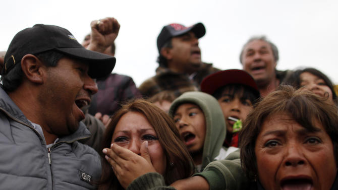 FILE - In this Oct. 13, 2010 file photo. Roxana Gomez, center, daughter of miner Mario Gomez, cries while watching on TV her father's rescue, as Maria Segovia, right, sister of trapped miner Dario Segovia, cheers, at the camp outside the San Jose mine near Copiapo, Chile. One of the myths surrounding the 33 miners who survived 69 days, 700 feet deep, and whose unprecedented and dramatic rescue was beamed to millions around the world, is that they are millionaires and do not need work. A year after the tragedy, nearly half are unemployed, one lives the fame that began to take shape at the bottom of the mine, many have chosen to give motivational talks to make a living and four returned to work in the mines.  (AP Photo/Natacha Pisarenko, File)