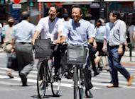 This file photo shows cyclists crossing a road in Tokyo, in July. Private consumption, which accounts for some 60 percent of the Japanese economy, expanded 0.1 percent in the three months to June, dropping steeply from a 1.2 percent expansion marked in the previous quarter