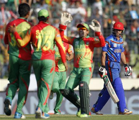 Afghanistan's Shafiqullah leaves field as Bangladesh's fielders celebrate his dismissal during ICC Twenty20 World Cup match in Dhaka