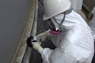 Image taken by TEPCO on September 4, 2013 shows a worker checking radiation levels at a water tank at the Fukushima nuclear power plant. Vapour has begun rising again from a reactor at the plant, more than two-and-a-half years after its core melted down, TEPCO said Friday