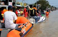 Residents use rafts and jet skies to travel down a street flooded in the aftermath of Typhoon Nalgae in Calumpit. The Philippines deployed helicopters, inflatable boats and amphibious vehicles Sunday in a desperate bid to evacuate tens of thousands in the aftermath of successive monster storms