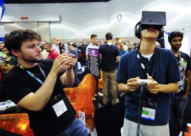 "Software designer Julian Kantor (L), who created ""The Recital"", takes a picture of Jonathan Feng using the Oculus Rift virtual reality headset to experience his program during E3 in Los Angeles, California in this June 12, 2013 file photo. Facebook Inc will acquire two-year-old Oculus VR Inc, a maker of virtual-reality glasses for gaming, for $2 billion, buying its way into the fast-growing wearable devices arena with its first-ever hardware deal. On March 25, 2014, Facebook said virtual-reality technology could emerge as the next social and communications platform. REUTERS/Gus Ruelas/Files (UNITED STATES - Tags: SOCIETY BUSINESS SCIENCE TECHNOLOGY)"