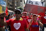 Supporters of Venezuelan President Hugo Chavez march during a massive gathering outside Miraflores presidential palace in homage of Chavez, in Caracas, on January 10, 2013. With Chavez ailing and absent, Venezuela's leftist government launches a new presidential term with a display of popular support on the day he was to be inaugurated
