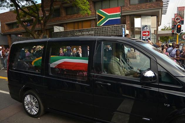 The funeral cortege of South African former president Nelson Mandela drives through the streets in Pretoria on December 11, 2013 to the Union Buildings to mark the start of a three-day lying in state