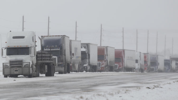 A long line of tractor trailers sits idle along Interstate 70 eastbound near Watkins, Colo., at a roadblock to close the highway as a spring storm packing high winds and heavy snow sweeps over Colorado's Front Range and on to the eastern plains on Saturday, March 23, 2013. Forecasters predict up to a foot of snow will fall in some locations in Colorado before the storm heads toward the nation's midsection. (AP Photo/David Zalubowski)