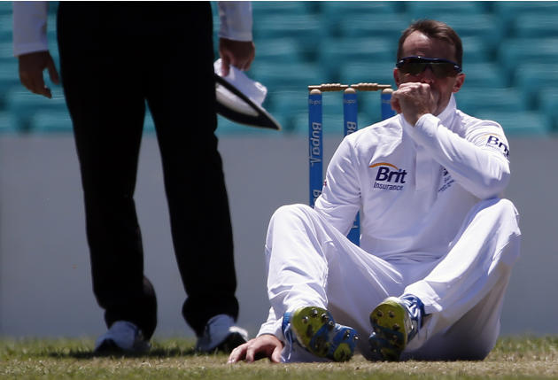 England's Swann sits on the ground after falling while bowling to Cricket Australia Invitational Xi's Cowan during their warm-up match at the Sydney Cricket Ground