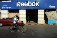 A cyclist rides past a Reebok store in Mumbai in April. Police have arrested five former senior executives of Reebok India for allegedly defrauding the sportswear company of about $160 million over a number of years, police said on Thursday