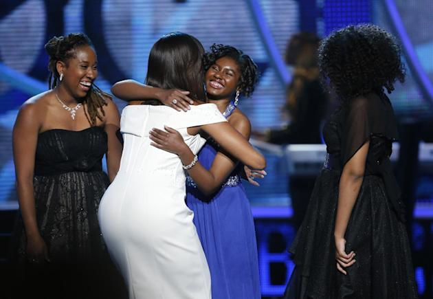 First Lady Michelle Obama, center left, hugs Making A Difference award winner Chental-Song Bembry, center right, as M.A.D. winners Kaya Thomas, left, and Gabrielle Jordan look on during a taping of th