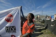 A woman holds an AIDS awareness banner in Cape Town, South Africa, in 2011. Deaths from HIV/AIDS are rising in parts of Asia and central Europe and the global response must accelerate, experts said after the release of a major report on the world AIDS epidemic