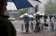 File picture shows members of the media shielding themselves from a rainstorm in Washington, DC