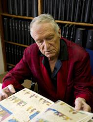 In this Oct. 13, 2011 photo, American magazine publisher, founder and Chief Creative Officer of Playboy Enterprises, Hugh Hefner is seen surrounded by books at his home at the Playboy Mansion in Beverly Hills, Calif. (AP Photo/Kristian Dowling)