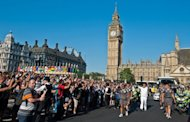 Anthony Page runs with the Olympic Torch through Parliament Square during the London 2012 Olympic Torch Relay, on July 26. Costing �9.3 billion ($14.5 billion) and featuring more than 10,000 athletes, the four-yearly sporting extravaganza will open officially after a rollercoaster build-up