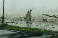 People walk along the Han river in the central Vietnamese coastal city of Da Nang on October 15, 2013 as Typhoon Nari hit
