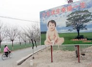 A woman cycles past a billboard encouraging couples to have only one child in a suburb of Beijing. Chinese authorities say a woman was forced to abort seven months into her pregnancy, several days after her plight came to light when images of her baby's corpse were posted online