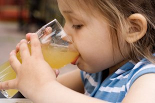 Young girl drinking juice.