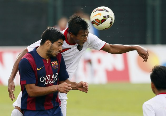 Barcelona's Luis Suarez (L) fights for the ball with Indonesia U19 player Putu Gede during a friendly soccer match near Barcelona September 24, 2014. REUTERS/Albert Gea (SPAIN - Tags: SPORT SOCCER)