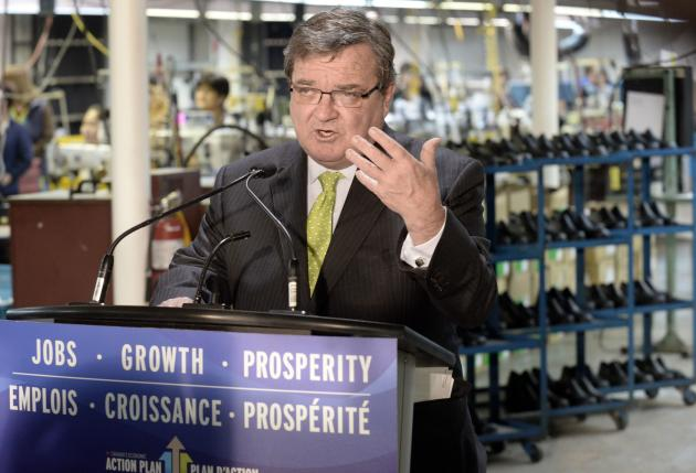 Minister of Finance Jim Flaherty speaks after trying on a new pair of shoes during a pre-budget photo opportunity at Mellow Walk Footwear in Toronto, February 7, 2014. REUTERS/Aaron Harris (CANADA - Tags: POLITICS)