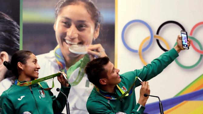 Maria Guadalupe Gonzalez, athletics silver medalist and German Sanchez, diving Olympic silver medalist take a selfie photo during a news conference after their return from the 2016 Rio Olympics at the international airport in Mexico City