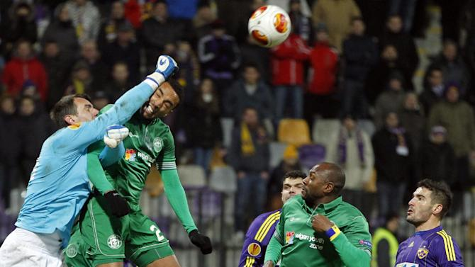 Maribor's goalkeeper Jasmin Handanovic, left, makes a save in front of Wigan's Jean Beausejour, center left, during their group D Europa League soccer match, in Maribor, Slovenia, Thursday, Dec. 12, 2013