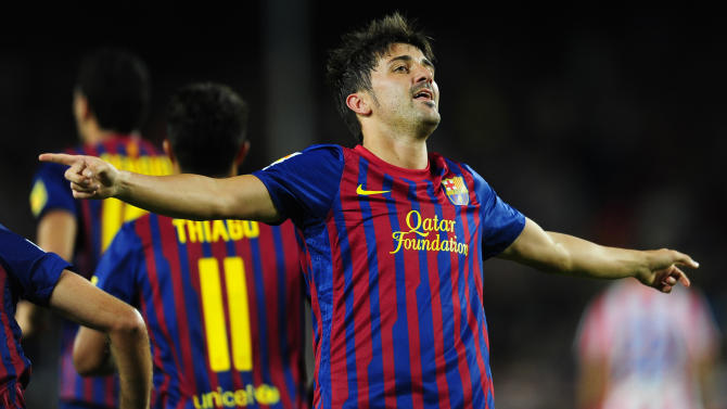 FC Barcelona's David Villa, right, reacts after scoring against Atletico Madrid during a Spanish La Liga soccer match at the Camp Nou stadium in Barcelona, Spain, Saturday, Sept. 24, 2011. (AP Photo/Manu Fernandez)