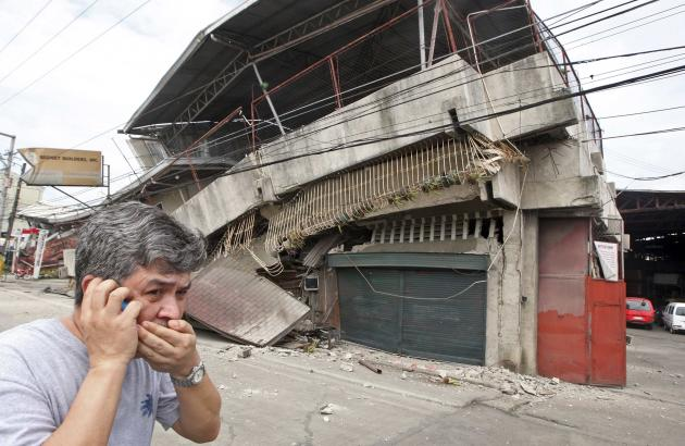 A resident walks past a building that collapsed during an earthquake in Cebu City