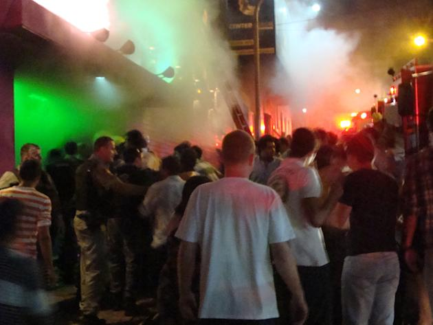 A crowd stands outside the Kiss nightclub during a fire inside the club in Santa Maria city,  Rio Grande do Sul state, Brazil, Sunday, Jan. 27, 2013.  A blaze raced through the crowded nightclub in so