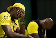 Jamaica's sprinter Usain Bolt laughs beside teammate Asafa Powell during a press conference by the Jamaica Olympic Association ahead of the 2012 London Olympic Games in London. Bolt will be Jamaica's flag bearer at the opening ceremony of the 2012 London Olympic Games