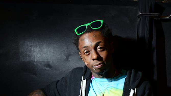 Recording artist Lil Wayne meets fans and celebrates his contemporary street wear apparel brand TRUKFIT at his hometown Macy's on Friday, Feb. 1, 2013 in New Orleans. (Photo by Jordan Strauss/Invision/AP)