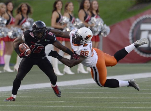 Ottawa Redblacks' Jock Sanders (19) is stopped B.C. Lions' Ese Mrabure-Ajufo (98) as he runs back a punt return during second half CFL action in Ottawa on Saturday July 4, 2015. THE CANADIAN P