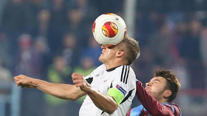 Trabzonspor's Yusuf Erdogan, right, and  Rzezniczak of Legia fight for the ball during their Europa League Group J soccer match in Trabzon, Turkey, Thursday, Oct. 24, 2013. (AP Photo)