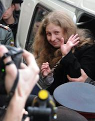 Maria Alyokhina, a member of female Russian punk band Pussy Riot, waves as she is escorted to the court in Moscow on Thursday. The court extended until late June the pretrial detention of two young members of the band whose stunt performance in Russia's main cathedral has drawn fury from the Church