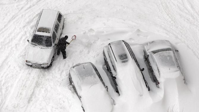 A driver shovels snow from his car in Kiev, Ukraine, Saturday, March 23, 2013. Heavy snow storms from the Balkan region have  stricken Ukraine. (AP Photo/Efrem Lukatsky)