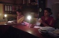 File photo shows office staff working by candlelight during a power cut in New Delhi. Industry leaders say electricity shortages have become a major obstacle to economic growth in the country, which has an installed power generation capacity of 187 gigawatts -- about 20 percent of China's level