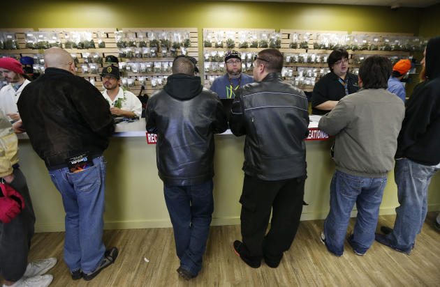 Employees help customers at the crowded sales counter inside Medicine Man marijuana retail store, which opened as a legal recreational retail outlet in Denver on Wednesday Jan. 1, 2014. Colorado began
