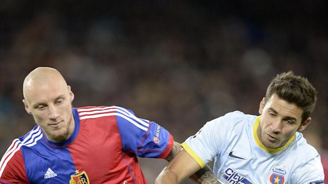 Basel's Ivan Ivanov, left, fights for the ball against Steaua's Lucian Filip, during a Champions League group E group stage match between Switzerland's FC Basel 1893 and Romania's FC Steaua Bucharest at the St. Jakob-Park stadium in Basel, Switzerland, Wednesday, Nov. 6, 2013