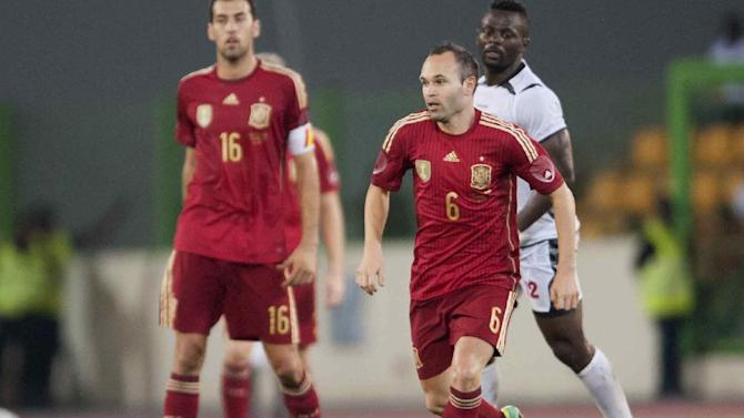 Spain's Andres Iniesta in action with  Equatorial Guinea's Thierry Fidjeu, right, during their friendly soccer match at Malabo Stadium in Malabo, Equatorial Guinea, Saturday, Nov. 16, 2013