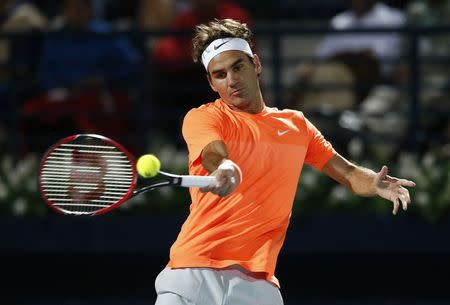 Roger Federer returns the ball to Novak Djokovic during their final match at the ATP Championships tennis tournament in Dubai