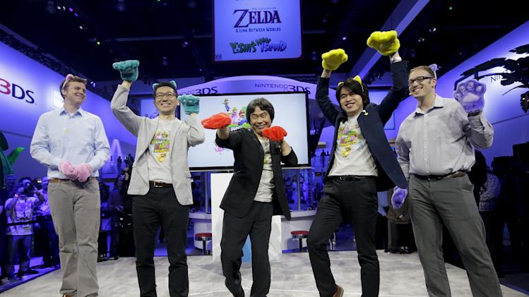 Shigeru Miyamoto, Center, a Japanese video game designer, is joined by game demonstrators and interpreters gestures while introducing the Super Mario 3D World at the Nintendo Wii U software showcase during the E3 game show in Los Angeles, Tuesday, June 11, 2013. (AP Photo/Jae C. Hong)