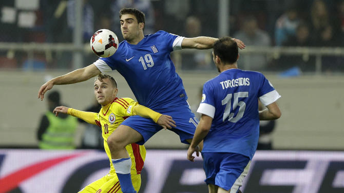 Greece's Sokratis Papstathopoulos (19) jumps for the ball with Romania's Alexandru Iulian Maxim during their World Cup qualifying playoff first leg soccer match at the Karaiskaki stadium in the port of Piraeus, near Athens, Friday, Nov. 15, 2013. Greece won 3-1