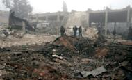 A handout picture released by the Syrian Arab News Agency shows Syrians inspecting the site of a suicide car bombing in Salmiyeh, a town in the central province of Hama, on January 22, 2013.